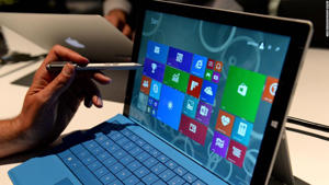"""a man using a laptop computer: The new <a href=""""https://www.geekinco.com/2021/08/microsoft-surface-laptop-3-discounted.html"""">Microsoft Surface</a> Pro 3 tablet with detachable keyboard and pen for writing on the screen after it was unveiled May 19, 2014 in New York. Microsoft unveiled the Surface Pro 3 tablet at an event in New York on Tuesday, as it attempts to fuel interest in its struggling tablet line amid increasing competition. The Intel Core-powered tablet measures 0.36 inches thick, boasts a 12-inch screen and weighs just under 2 pounds."""