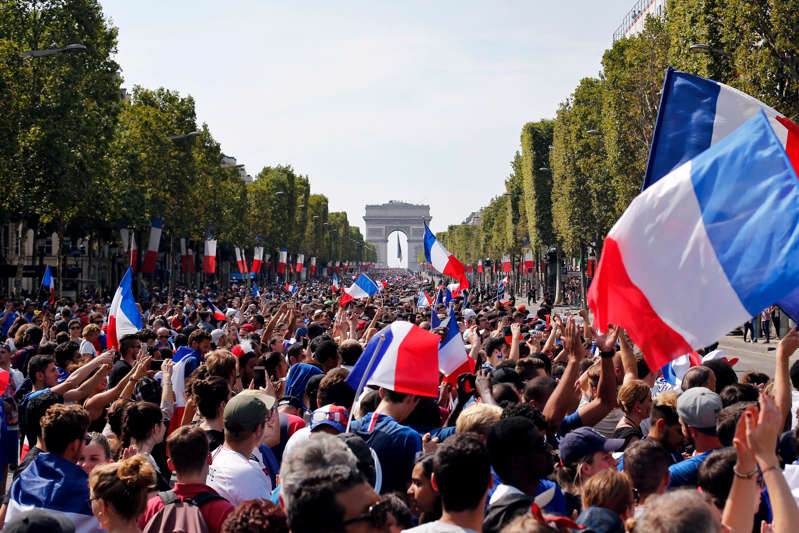 a group of people standing in front of a large crowd of people: French flags fly.