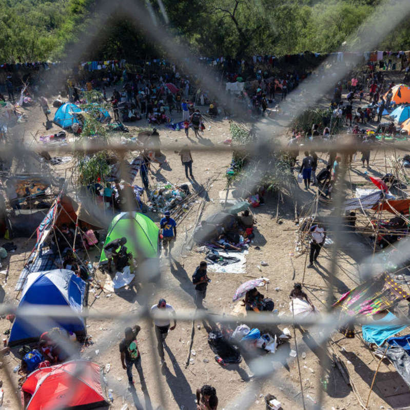 a group of people in a forest: Large Migration Surge Crosses Rio Grande Into Del Rio, Texas