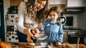 Mother and daughter in kitchen dusting cake with powdered sugar