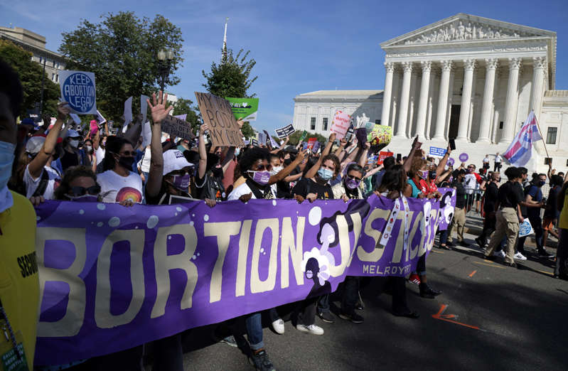 Women rights activists participate in the annual Women's March as they pass by the U.S. Supreme Court October 2, 2021 in Washington, DC.