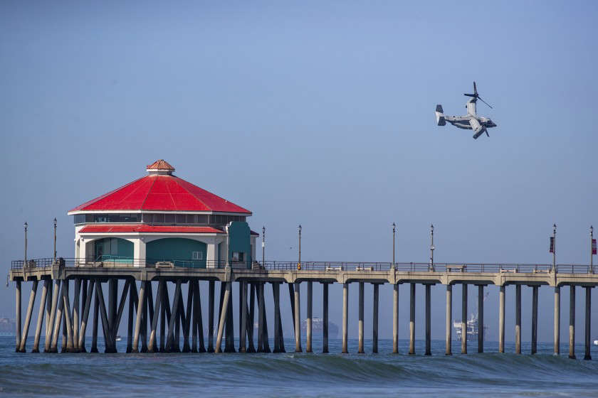 A U.S. Marine Corps MV-22 Osprey banks over the Huntington Beach Pier during the Pacific Airshow on Friday. (Brian van der Brug / Los Angeles Times)