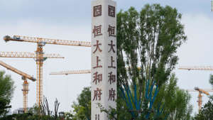 Cranes stand near Evergrande's name and logo at a new housing development in Beijing.