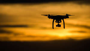 Can you fly a drone at night? image shows drone flying against sunset