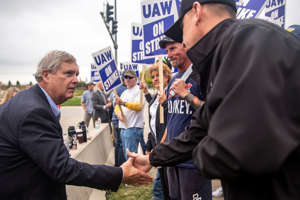 U.S. Secretary of Agriculture Tom Vilsack visits with picketers on strike outside Deere & Co.'s Des Moines Works on Wednesday in Ankeny.