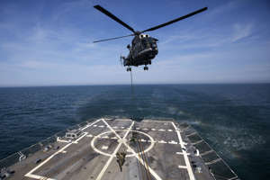 A Romanian special forces member disembarks from a helicopter onto the U.S. Navy destroyer USS Truxtun during a joint military drill in the Black Sea in 2014.
