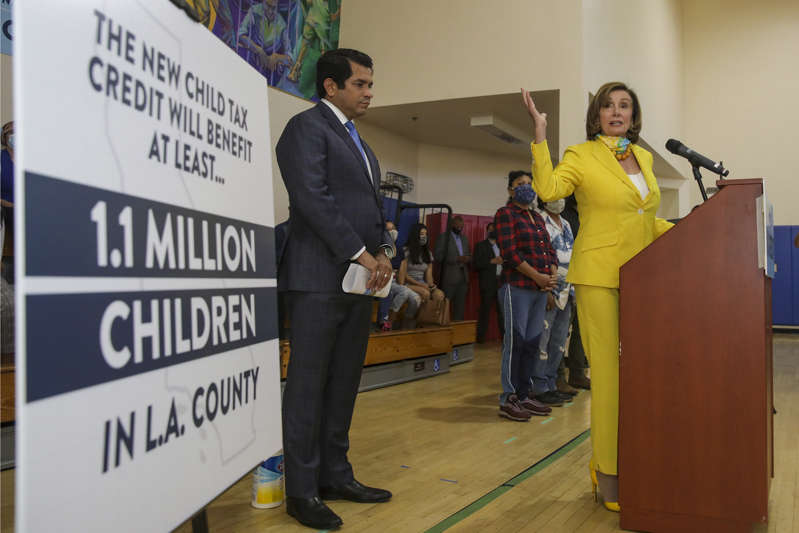 Representative Jimmy Gomez, left, watches as House Speaker Nancy Pelosi, talks about the expanded Child Tax Credit at a press conference held at Barrio Action Youth and Family Center on July 15, 2021 in Los Angeles, CA. (Irfan Khan / Los Angeles Times via Getty Images)