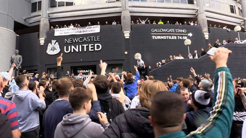 Newcastle United fans celebrate the club's Saudi takeover outside St James' Park
