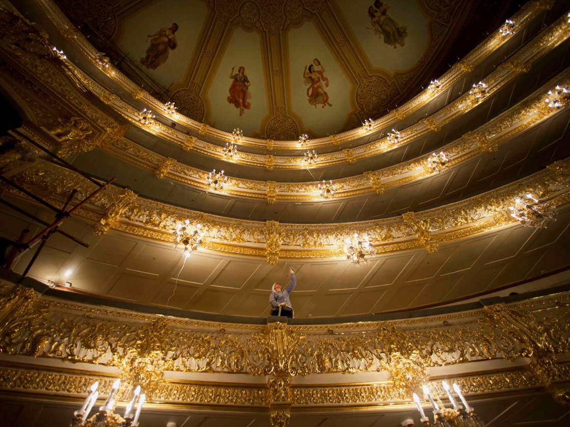 A restorer adds the final touches on the ceiling of a balcony in the big hall of the Bolshoi Theatre, in Moscow, Russia, Thursday, June 23, 2011, during a press tour organized by restorers. / Credit: AP Photo/Alexander Zemlianichenko