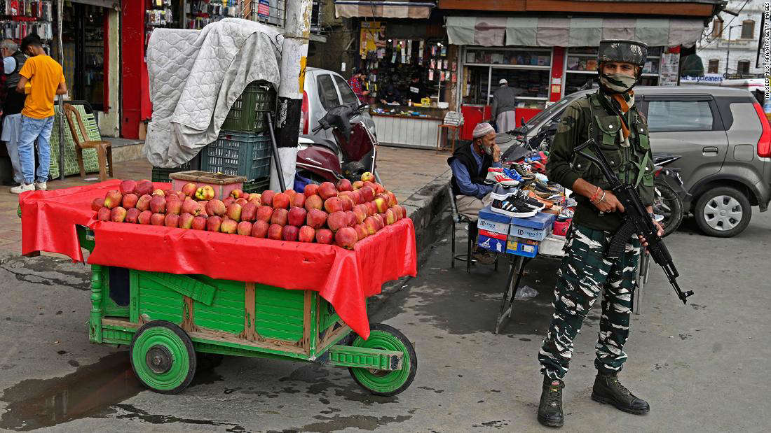 A member of the Indian security forces stands guard at a market in Srinagar on October 11.