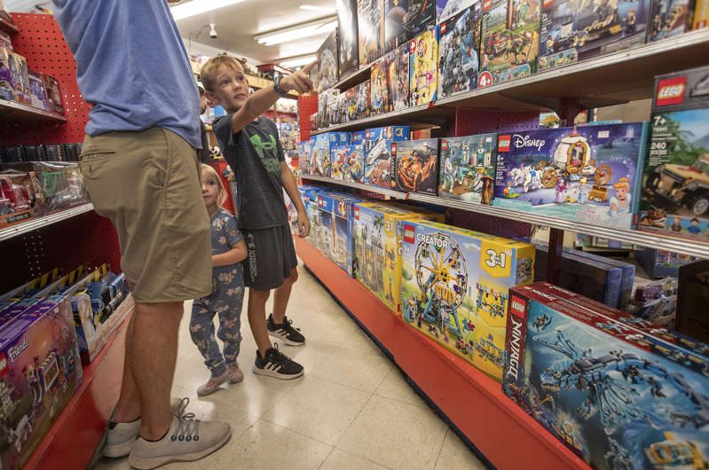 Jack Norris, 7, his sister Avery, 2, and their father, Lance, left, visit Kip's Toyland, located inside the Old Farmer's Market in Los Angeles on Sept. 22, 2021.