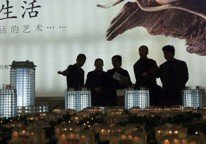 Potential buyers view models of new buildings at a real estate fair on March 17, 2005 in Shanghai, China. China now faces a potential financial disaster as its once hot real estate sector faces financial challenges.