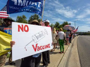 A protester holds an anti-vaccination sign as supporters of President Donald Trump rally in Woodland Hills, California on May 16, 2020. David McNew/Getty Images