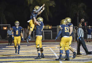 St. Thomas Aquinas running back Anthony Hankerson celebrates scoring a touchdown with offensive lineman Ryan Mickow during their game against Western on Sept. 24. The Raiders face Cardinal Gibbons on Saturday.