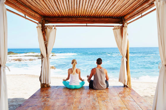 Slide 2 of 24: Couple meditating together in cabana overlooking ocean