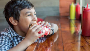 Mixed race boy eating burger in restaurant
