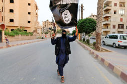 "A member loyal to the Islamic State in Iraq and the Levant (ISIL) waves an ISIL flag in Raqqa June 29, 2014. The offshoot of al Qaeda which has captured swathes of territory in Iraq and Syria has declared itself an Islamic ""Caliphate"" and called on factions worldwide to pledge their allegiance, a statement posted on jihadist websites said on Sunday. The group, previously known as the Islamic State in Iraq and the Levant (ISIL), also known as ISIS, has renamed itself ""Islamic State"" and proclaimed its leader Abu Bakr al-Baghadi as ""Caliph"" - the head of the state, the statement said."