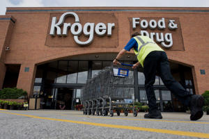 An employee pushes shopping carts towards a Kroger Co. store in Peoria, Illinois, U.S., on Tuesday, June 16, 2015.