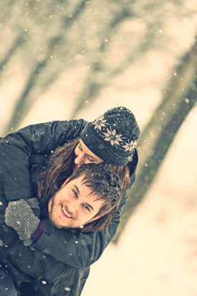 Slide 2 of 16: Happy young couple in winter