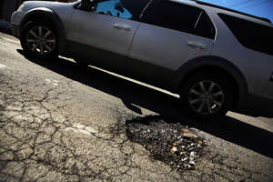 A car travels over a pothole on February 24, 2014 in the Brooklyn borough of New York City.