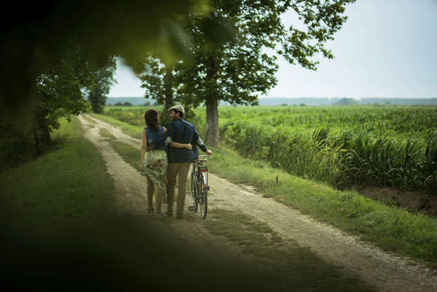 Slide 1 of 16: Rear view of a happy couple walking holding bike