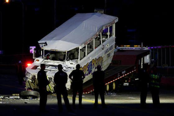 Police officers and other officials watch as a Ride the Ducks tourist vehicle is loaded onto a flat-bed tow truck in the late evening Thursday, Sept. 24, 2015, after it was involved in a fatal crash with a charter passenger bus earlier in the day in Seattle.