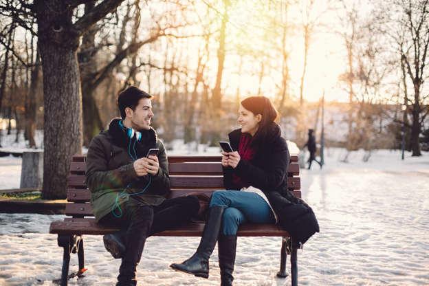Slide 1 of 25: Happy couple texting on smartphones
