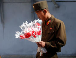 A soldier looks at decorative flowers outside of a shop Friday, Oct. 9, 2015, ah...
