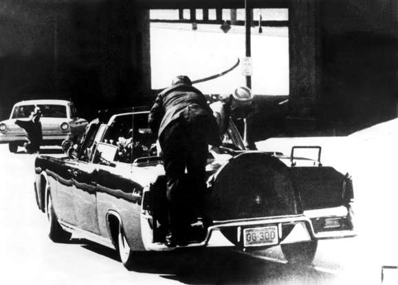Slide 4 de 25: JOHN F KENNEDY - 1963 A member of the Secret Service stands on the bumper of the presidential limousine in Dallas, seconds after President John F. Kennedy was shot. The President is in the back seat to the left, Mrs. Kennedy is standing up in the back seat to the right.