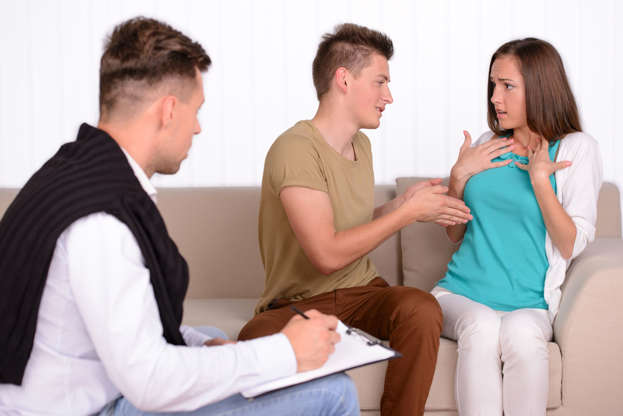 Slide 27 de 27: Young couple talking with family psychologist to solve their problems.