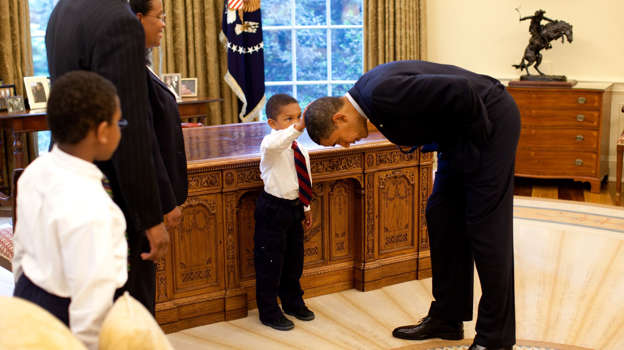 WASHINGTON - MAY 8: In this handout from the The White House, U.S. President Barack Obama bends over so the son of a White House staff member can pat his head during a visit to the Oval Office May 8, 2009 in Washington, DC. (Photo by Pete Souza/The White House/Getty Images)