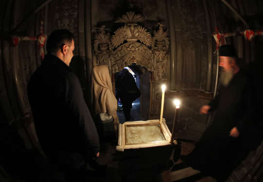 Christian worshippers enter the Edicule surrounding the Tomb of Jesus (where his body is believed to have been laid) on November 4, 2016 at the Church of the Holy Sepulchre in Jerusalems Old City. The experts from the National Technical University of Athens for cultural heritage preservation removed the marble slab stone that covered the original tomb since the last restoration of the edicule on 1810 by Greek architect Nikolaos Komnenos. The Church of the Holy Sepulchre in Jerusalems Old City is traditionally believed to be the site of Jesuss burial and attracts every year millions of pilgrims from all over the world. / AFP / THOMAS COEX (Photo credit should read THOMAS COEX/AFP/Getty Images)