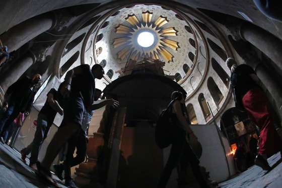 Christian worshippers visit the Edicule surrounding the Tomb of Jesus (where his body is believed to have been laid) as it is strengthened as part of the conservation work done by a Greek team of experts on November 4, 2016 at the Church of the Holy Sepulchre in Jerusalems Old City. The experts from the National Technical University of Athens for cultural heritage preservation removed the marble slab stone that covered the original tomb since the last restoration of the edicule on 1810 by Greek architect Nikolaos Komnenos. The Church of the Holy Sepulchre in Jerusalems Old City is traditionally believed to be the site of Jesuss burial and attracts every year millions of pilgrims from all over the world. / AFP / THOMAS COEX (Photo credit should read THOMAS COEX/AFP/Getty Images)