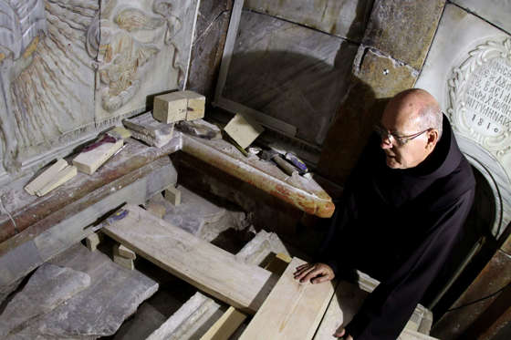 A Franciscan friar looks at the exposed the Tomb of Jesus, where his body is believed to have been laid, as part of conservation work done by a team of Greek team of preservation experts in Jerusalem on late on October 28, 2016. The experts from the National Technical University of Athens for cultural heritage preservation removed the marble slab stone that covered the original tomb since the last restoration of the edicule on 1810 by Greek architect Nikolaos Komnenos. The Church of the Holy Sepulchre in Jerusalems Old City is traditionally believed to be the site of Jesuss burial and attracts every year millions of pilgrims from all over the world. / AFP / GALI TIBBON (Photo credit should read GALI TIBBON/AFP/Getty Images)