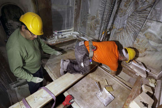 Greek preservation experts place back the marble slab stone that covered the Tomb of Jesus, where his body is believed to have been laid, after it was removed for 3 days to allow the team to do restoration works and study as part of conservation work done by the Greek team in Jerusalem on late on October 28, 2016. The experts from the National Technical University of Athens for cultural heritage preservation removed the marble slab stone that covered the original tomb since the last restoration of the edicule on 1810 by Greek architect Nikolaos Komnenos. The Church of the Holy Sepulchre in Jerusalems Old City is traditionally believed to be the site of Jesuss burial and attracts every year millions of pilgrims from all over the world. / AFP / GALI TIBBON (Photo credit should read GALI TIBBON/AFP/Getty Images)