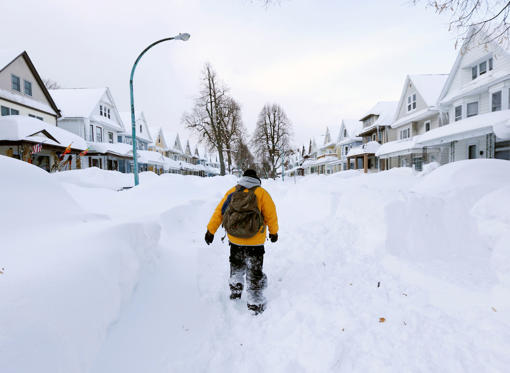 FILE - Brian Cintron walks in his snow-bound south Buffalo neighborhood on Thursday, Nov. 20, 2014, in Buffalo, N.Y. A new blast of lake-effect snow pounded Buffalo for a third day piling more misery on a city already buried by an epic, deadly snowfall t