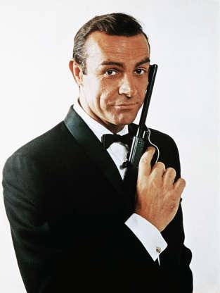 Διαφάνεια 29 από 45: (Original Caption) Waist-up portrait of Sean Connery, as James Bond, caressing the barrel of a gun against the side of his face. Connery is wearing a tuxedo and bow tie and smiling slightly.