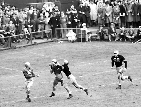 Slide 5 of 10: Notre Dame Back Emil Sitko (14) grabs a pass intended for Army Back Bill West (36) (right) during the fourth quarter of the Notre Dame-Army at Yankee Stadium, Nov. 9, 1946, New York. Notre Dame Quarterback John Lujack (32) holds out hands for possible lateral. Game ended in a scoreless tie.