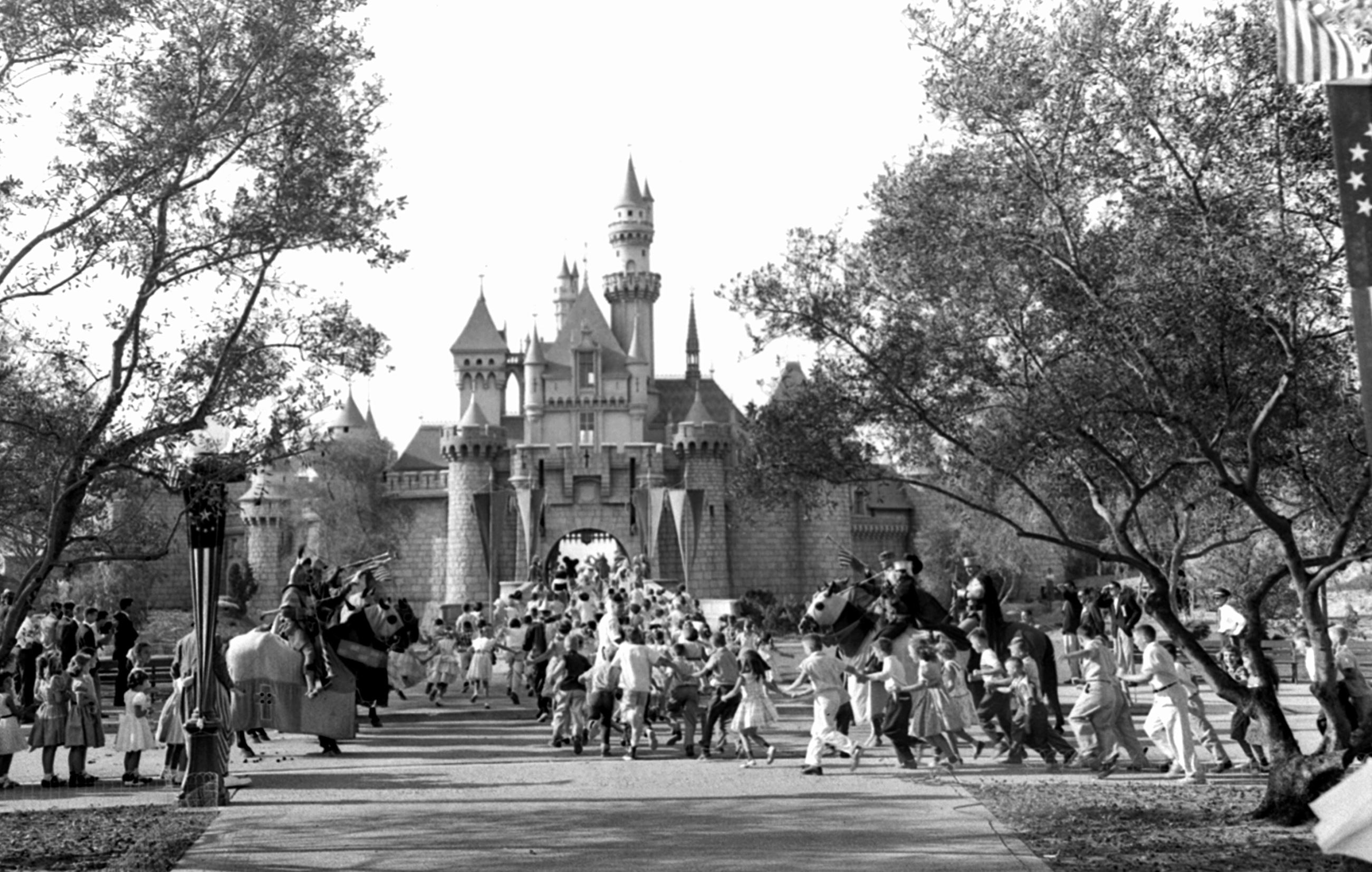 Slide 2 of 33: FILE - In this Sunday, July 17, 1955 file photo, children sprint across a drawbridge and into a castle that marks the entrance to Fantasyland at the opening of Walt Disney's Disneyland in Anaheim, Calif. Fantasyland had been closed until late in the day.
