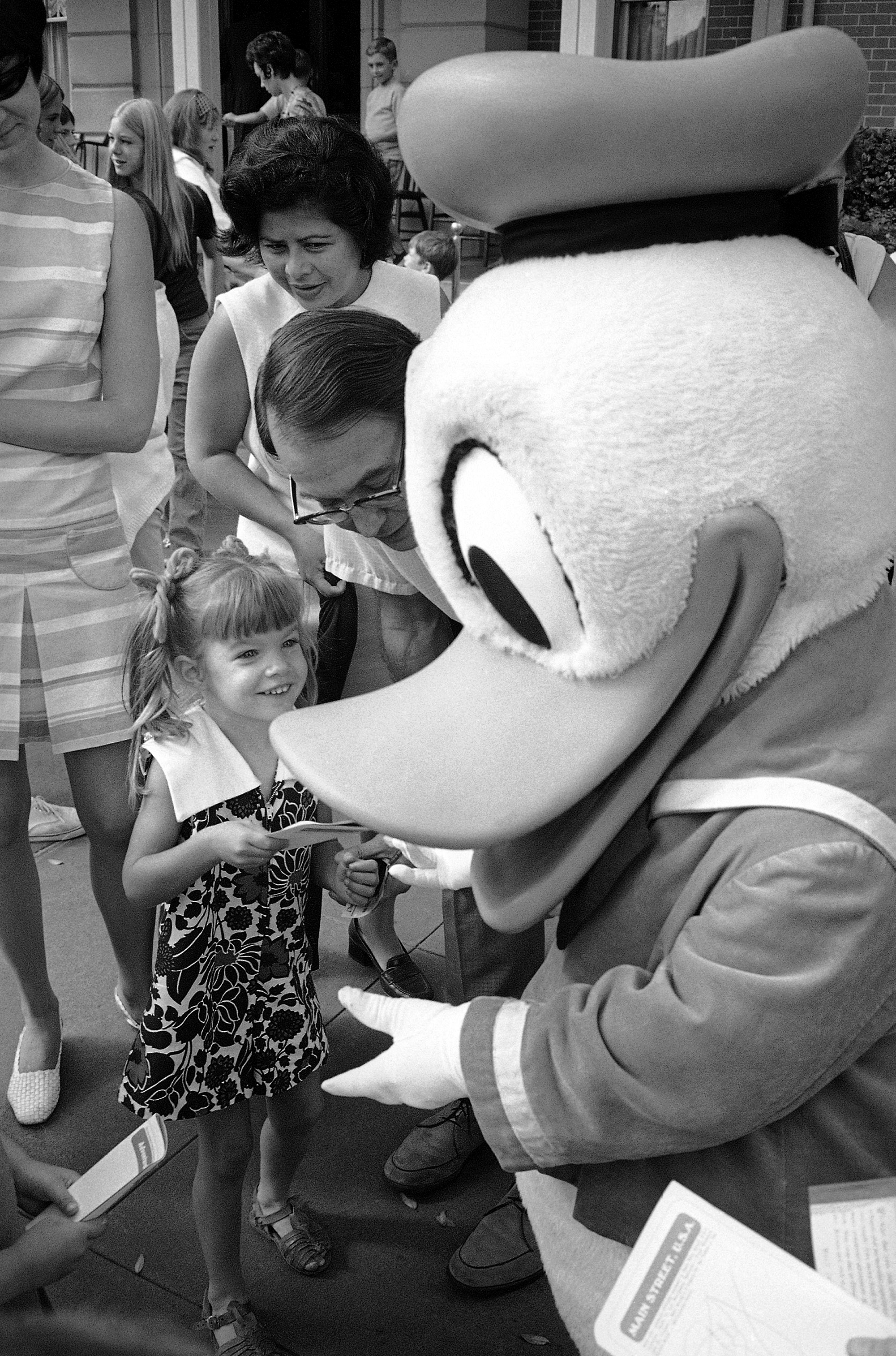 Slide 24 of 33: A delighted little girl meets a larger-than life celebrity at the Magic Kingdom of Disneyland, in Anaheim, Orange County, Calif., Feb. 28, 1974. The county itself has been accused of being a giant playland, a place where people go to escape the problems