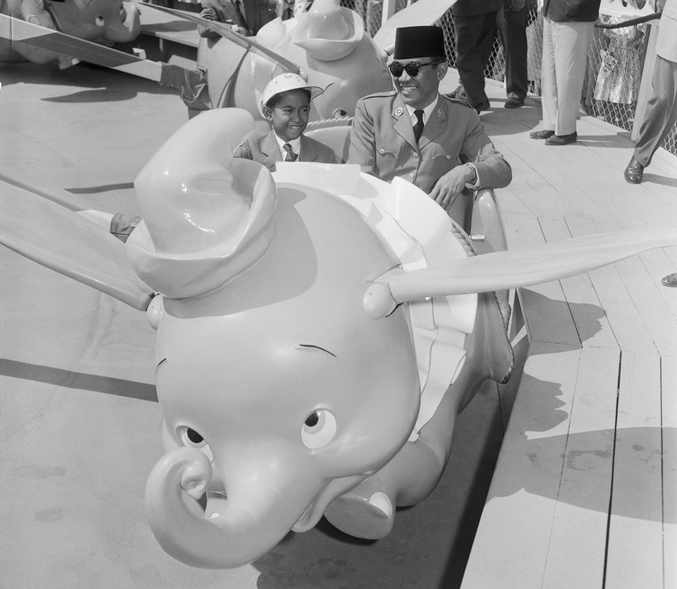 Slide 7 of 33: (Original Caption) 6/4/1956-Anaheim, California- Dr. Achmed Sukarno, President of Indonesia, now touring the US, is shown with his son, Guntur, 12, riding behind 'Dumbo,' one of the fabulous residents of Disneyland, during their visit to the famous playg
