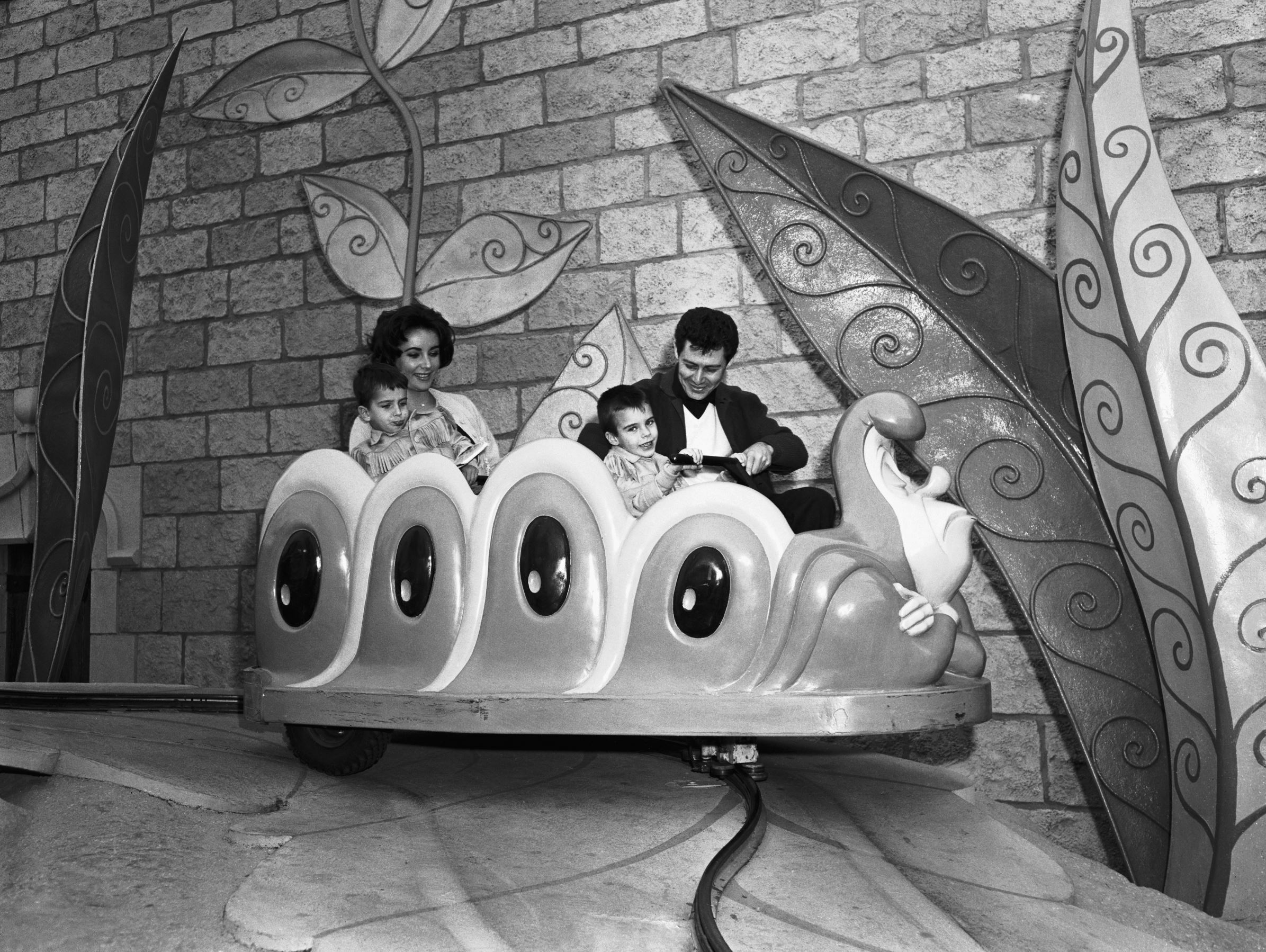Slide 15 of 33: (Original Caption) 1/22/1959-Anaheim, CA- Enjoying a visit to Disneyland here Jan. 21, Elizabeth Taylor and Eddie Fisher, try an amusement ride with two of Miss Taylor's sons, Christopher (left), 4, and Michael (right), 6. Both of the boys are sons of Mr