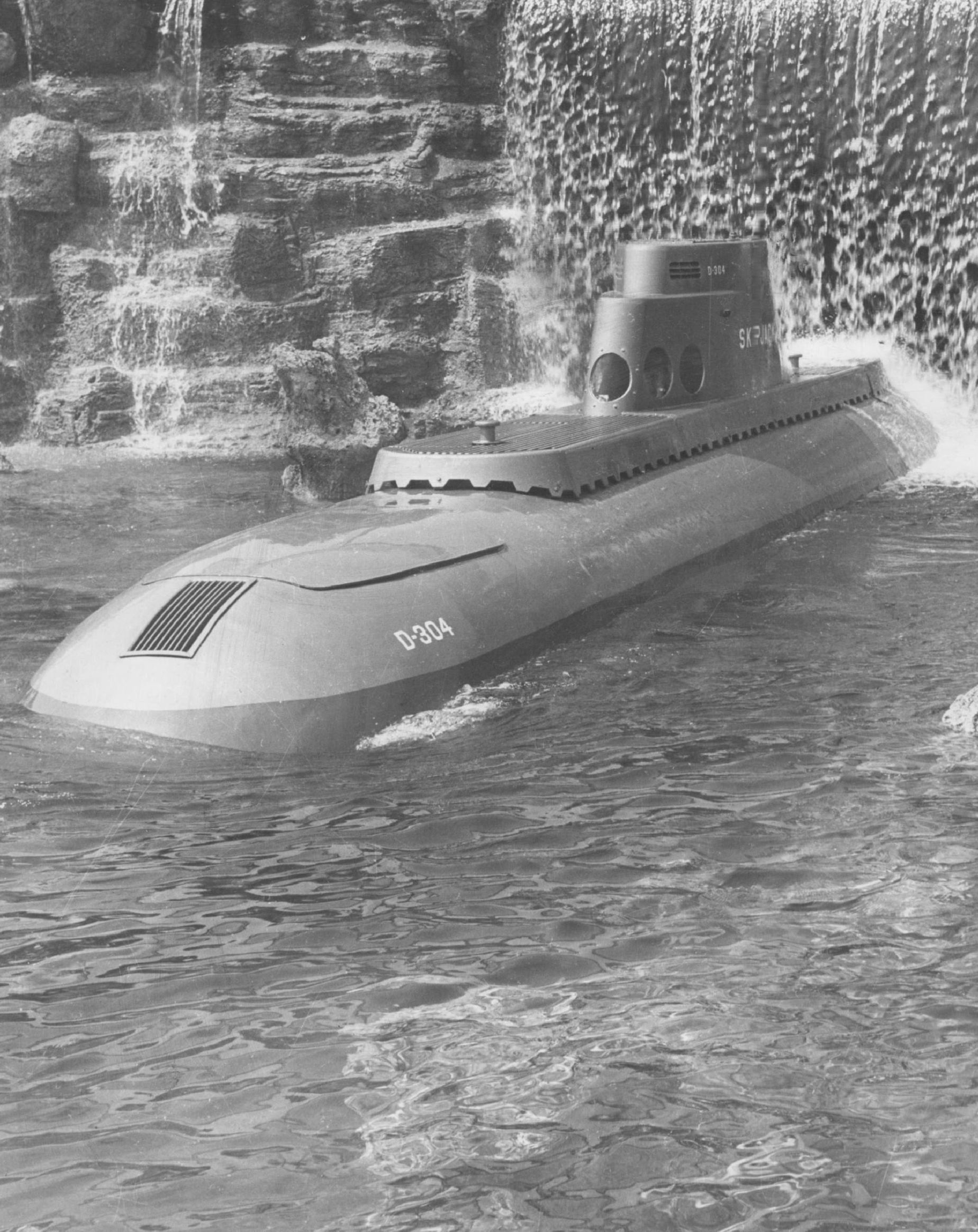 Slide 16 of 33: APR 8 1960; To Perform for Carriers; The 'Skipjack,' one of eight Disneyland Submarines named after America's nuclear powered undersea fleet, breaks through a cascading waterfall after its journey through 'liquid' space at the California amusement center