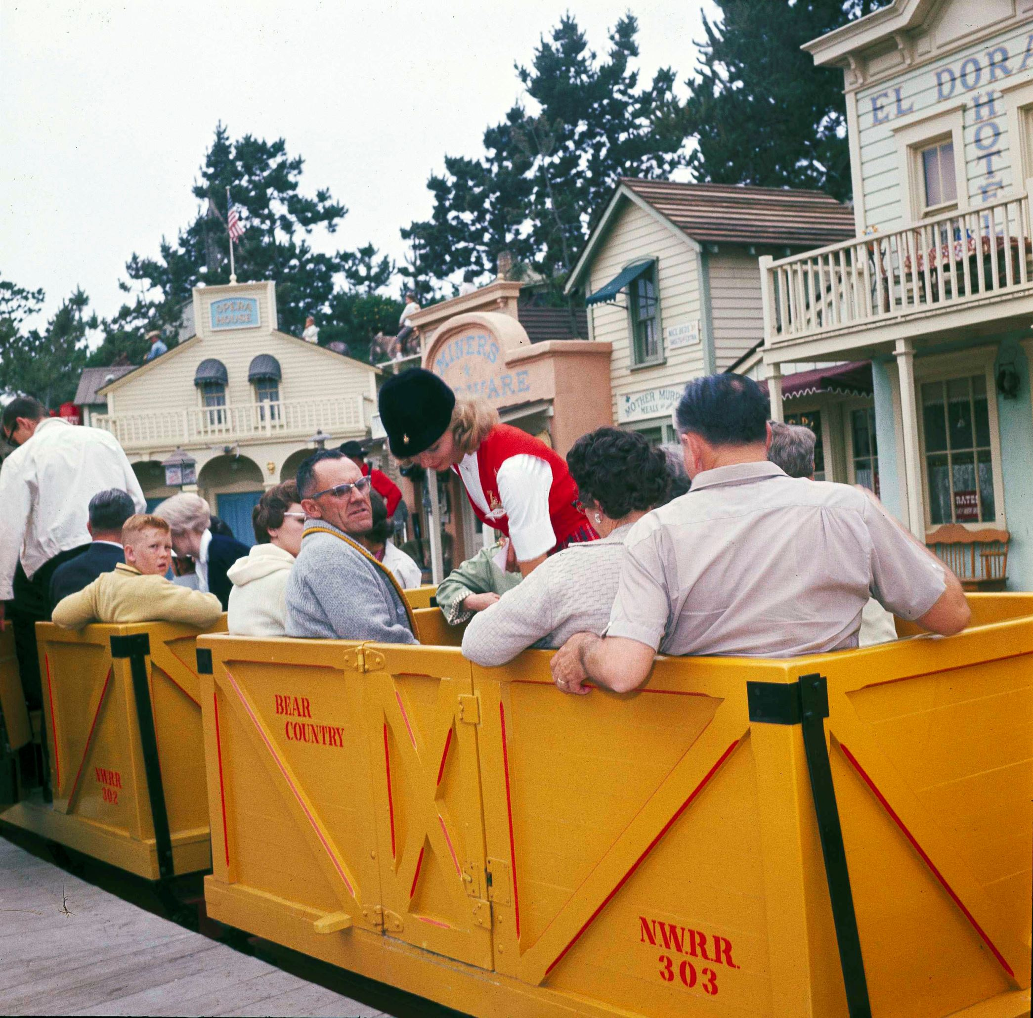 "Slide 18 of 33: Disneyland guide Diane Stewart, center, prepares tourists for a boxcar ride down ""Main Street"" at Disneyland in Anaheim, Calif., June 13, 1962. This section of Disneyland is built to the 1890 period. (AP Photo)"