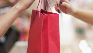 Woman handing over shopping bag retail