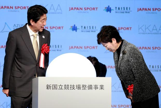 21 枚のスライドの 6 枚目: Japanese Prime Minister Shinzo Abe, left, is greeted by Tokyo Gov. Yuriko Koike after a groundbreaking ceremony of new national stadium in Tokyo, Sunday, Dec. 11, 2016.