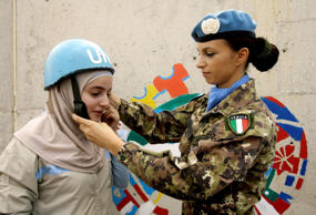 A Lebanese young girl is assisted by an Italian peacekeeper to wear a helmet in front of a painting on a wall of the United Nations Interim Force in Lebanon (UNIFIL) headquarters during the International Day of Peace in the southern Lebanese town of Naqu