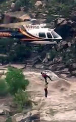 In this Sunday, July 23, 2017, image taken from video provided by the Pima County Sheriff's office, a stranded hiker is rescued from torrential flash flood waters near Tucson, Ariz. Over a dozen hikers were stranded Sunday in a scenic canyon on the outskirts of Tucson, just over a week after a flash flood killed 10 members of an extended family more than 140 miles to the north.
