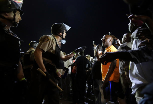 In this Aug. 10, 2015, file photo, officers and protesters face off along West Florissant Ave. in Ferguson, Mo., a year after the fatal police shooting of Michael Brown.