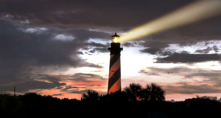 Слайд 14 из 17: Lighthouse at St. Augustine, Florida at sunset running its beam in a circular search pattern.